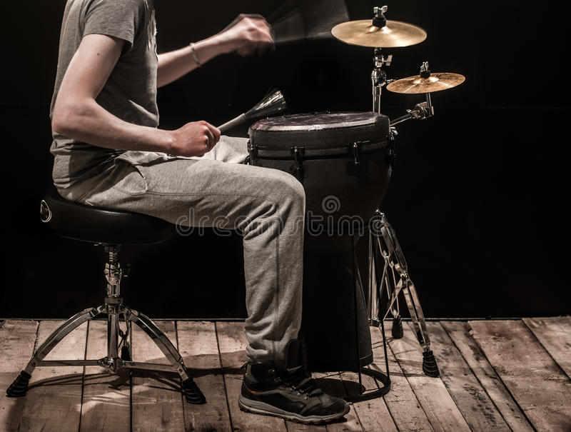 man playing a djembe drum and cymbals on a black background royalty free stock photo