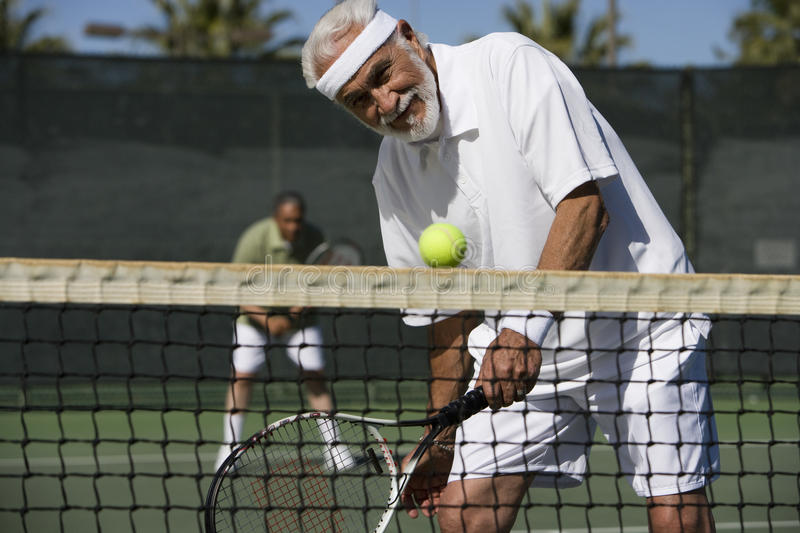 Man Playing Doubles On Tennis Court. Happy senior men playing doubles on tennis court royalty free stock photos