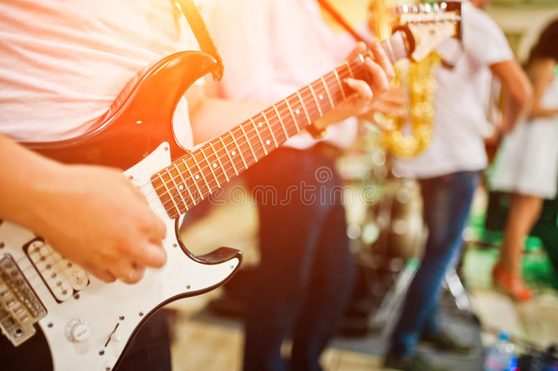 Man playing on electric guitar against band.  royalty free stock image
