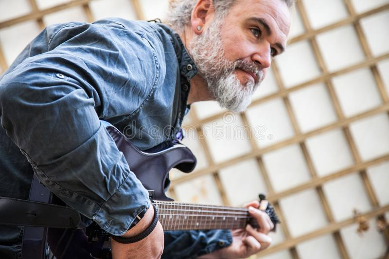 Man playing an electric guitar stock photo