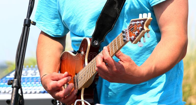 Man playing an electric guitar outside in a blue shire. Electric guitar being played outside by a man in a blue shirt royalty free stock images