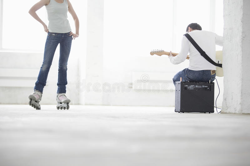 Man Playing Electric Guitar With Woman Wearing Inline Skate In W royalty free stock photography