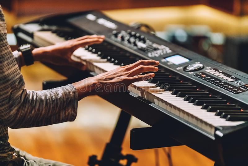 Man playing electronic musical keyboard synthesizer by hands on white and black keys in recording studio stock images