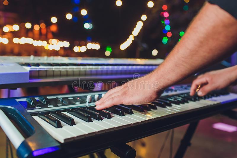 Man playing electronic musical keyboard synthesizer by hands on white and black keys in recording studio. royalty free stock image