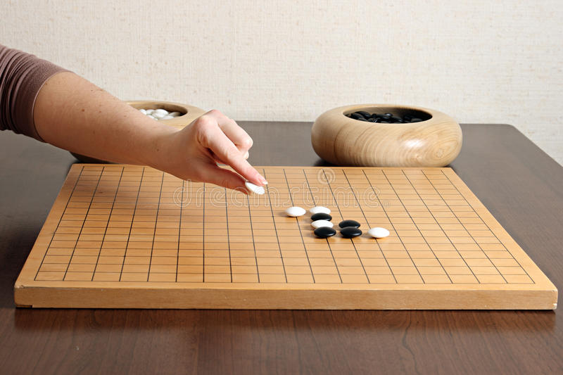 Man playing the game Go. Go player holding a white stone. Go is played on a grid of black lines (19×19). The playing pieces, called stones, are played on the stock images