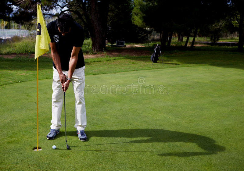 Man playing golf. Full length portrait of handsome golfer man in white pants and black t-shirt standing on golf course preparing to hit golf ball, good golf game stock photo