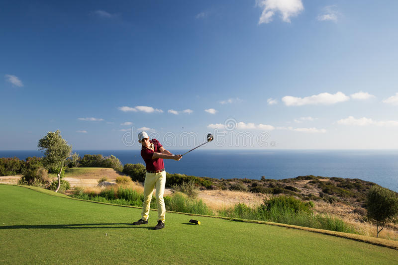 Man playing golf. Professional male golf player hitting by driver from tee royalty free stock image