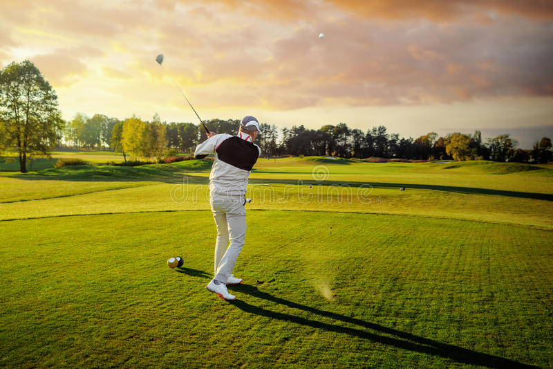 Man playing golf. Professional male golf player hitting by driver from tee stock photography
