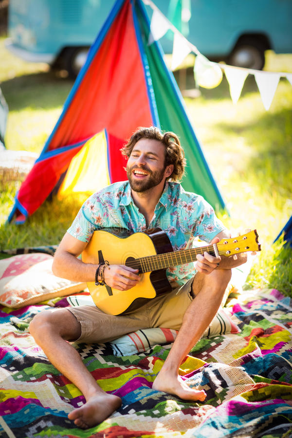 Man playing guitar at campsite. In park on a sunny day royalty free stock photos
