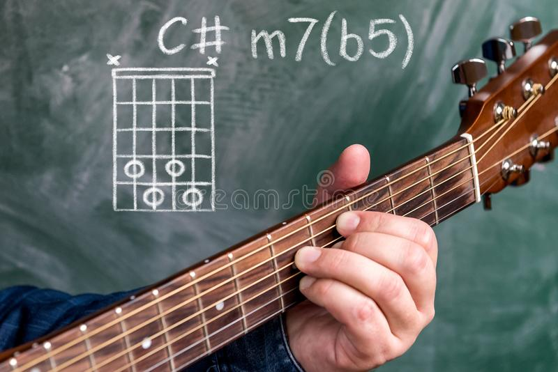 Man playing guitar chords displayed on a blackboard, Chord C minor 7b5. Man in a blue denim shirt playing guitar chords displayed on a blackboard, Chord C minor stock image