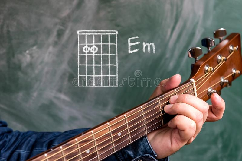 Man playing guitar chords displayed on a blackboard, Chord E minor. Man in a blue denim shirt playing guitar chords displayed on a blackboard, Chord E minor stock images