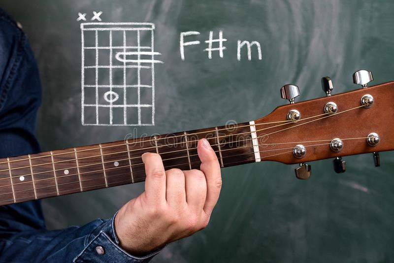 Man Playing Guitar Chords Displayed On A Blackboard Chord F Sharp M