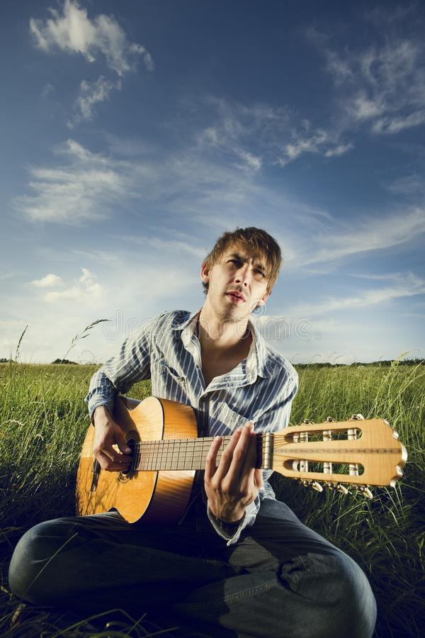 Man playing guitar on field stock photos