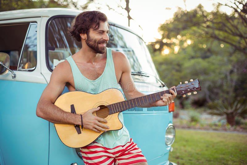 Man playing guitar in front of campervan at campsite. On a sunny day stock photos