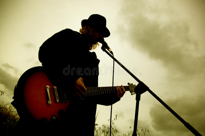 Man playing guitar outdoors. Sepia mood royalty free stock images