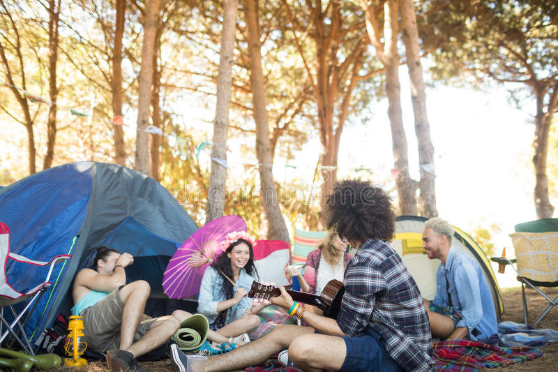 Man playing guitar while sitting with friends at campsite. Man playing guitar while sitting with friends on field at campsite stock photos