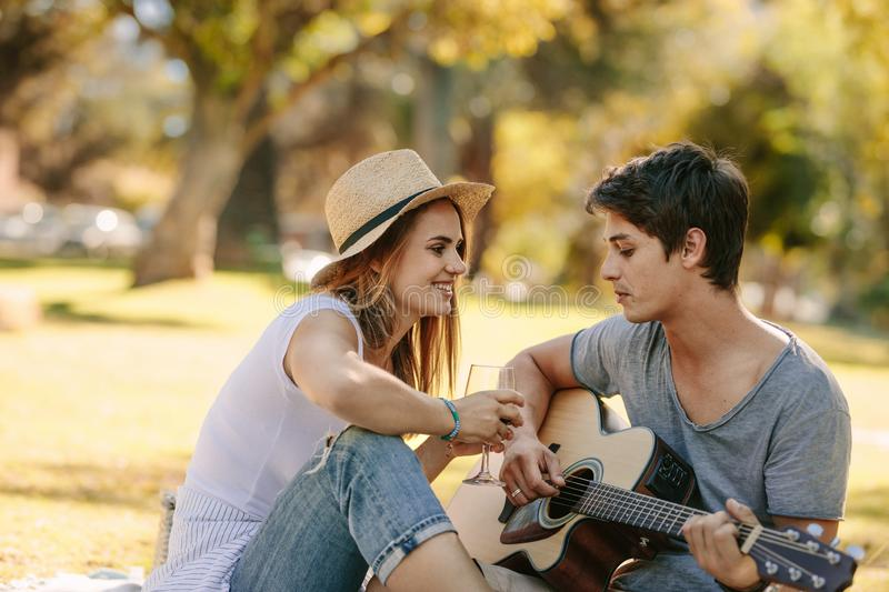 Couple on picnic sitting in a park having fun stock photography