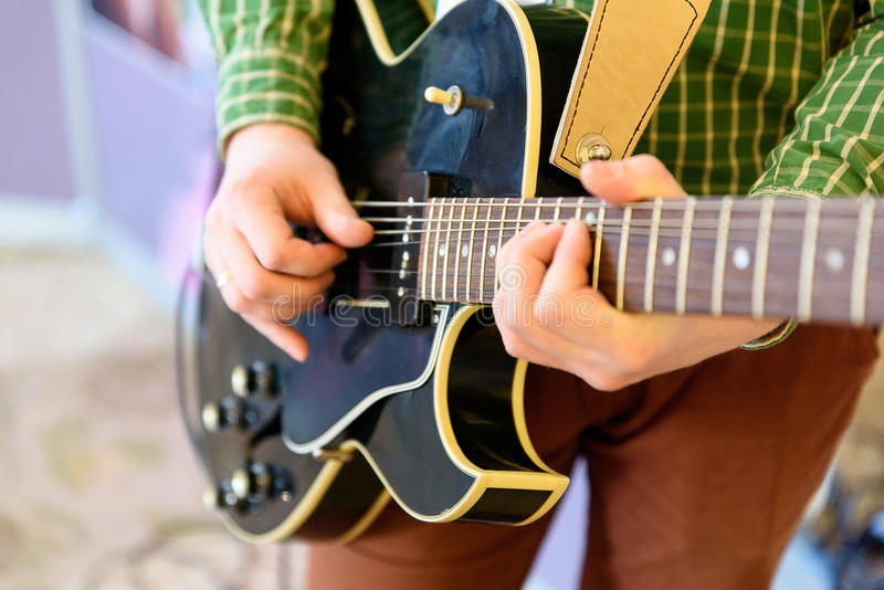 Man playing guitar on a stage. Musical concert. Close-up view.  stock photography