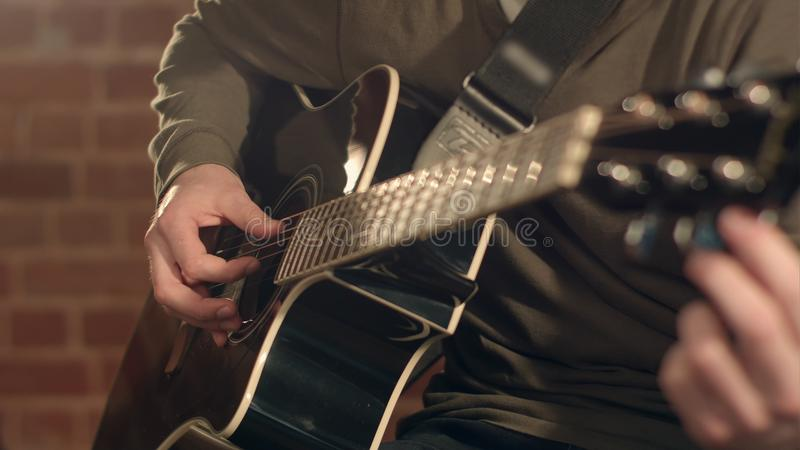 Man playing guitar on a stage. Musical concert. Close-up view. Professional shot in 4K resolution. You can use it e.g. in your commercial video, business stock image
