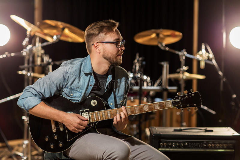 Man playing guitar at studio rehearsal. Music, people, musical instruments and entertainment concept - male guitarist playing electric guitar at studio rehearsal royalty free stock photo