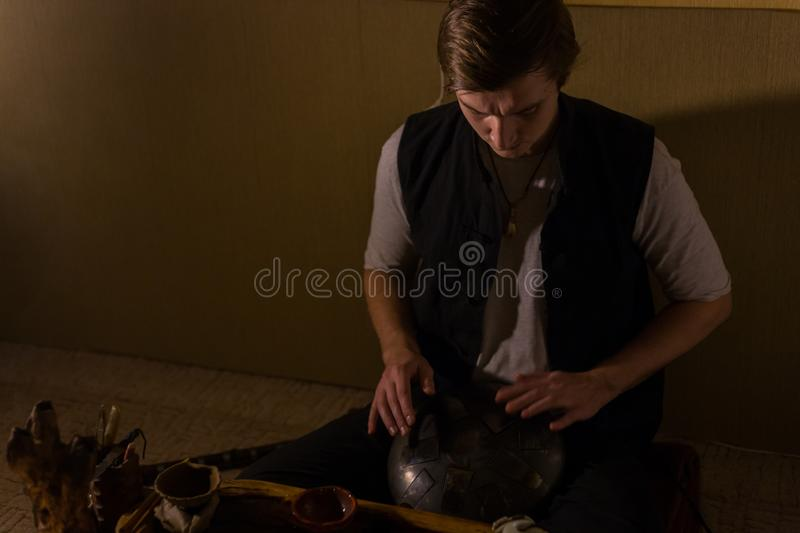 Man playing hang drum. Man playing tank drum or hang at home. Warm romantic illumination, low key. Relaxation, meditative and traditional music concept. Close up royalty free stock image