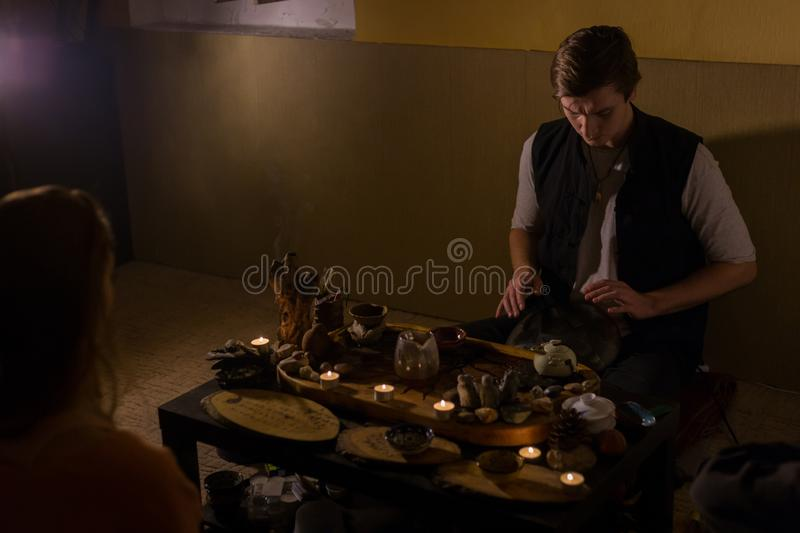 Man playing hang drum. Man playing tank drum or hang at home. Warm tic illumination, low key. Relaxation, meditative and traditional musioncept. Close up shot royalty free stock photography