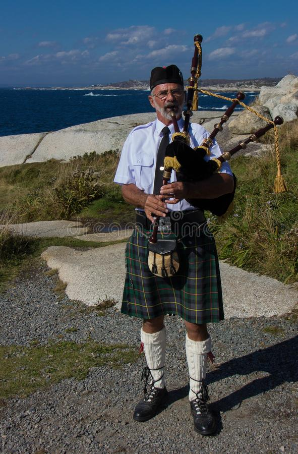 A Man Playing His Bagpipe. Along the rocky coastline of Nova Scotia, Canada royalty free stock photography