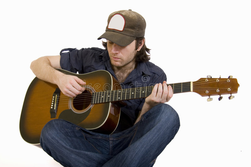 Man playing his guitar seated royalty free stock photo