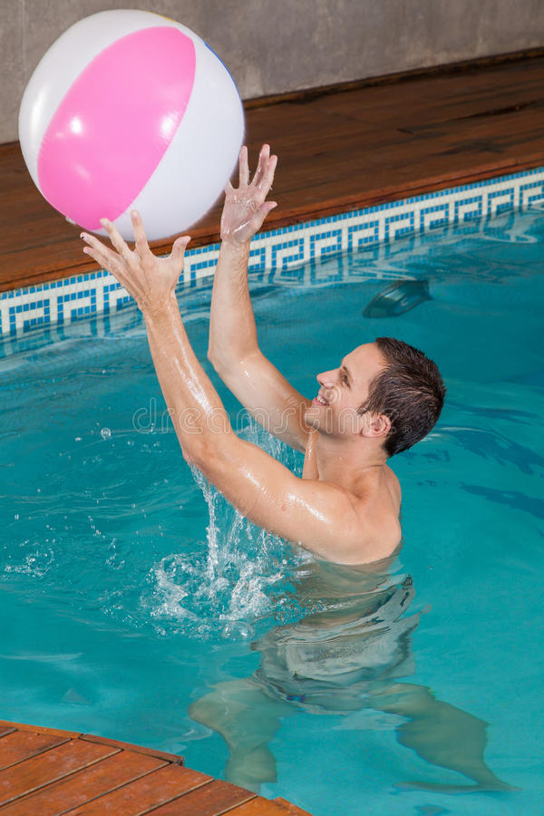 Man playing with inflatable ball inside the pool royalty free stock photos
