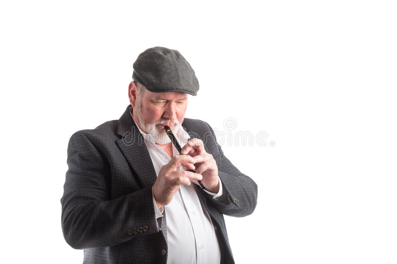 Man playing a Irish penny whistle. A man wearing a hat and blazer playing a Irish penny whistle, isolated on a white background stock photo