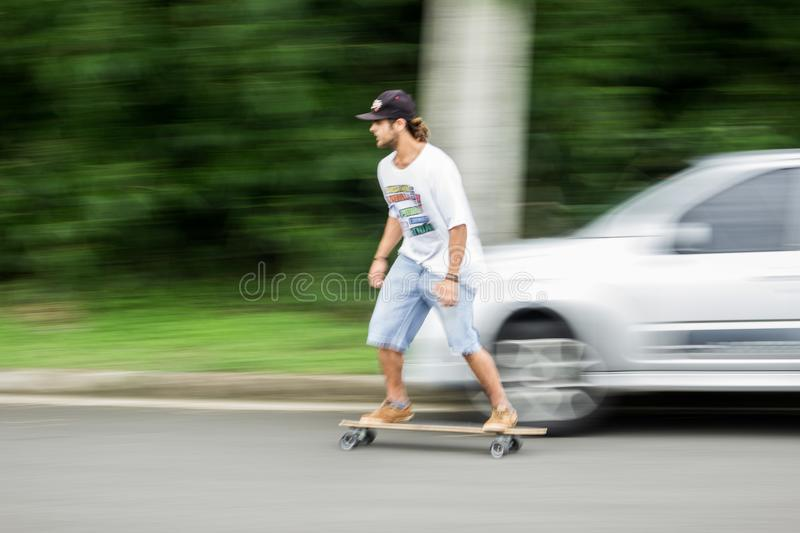 Man Playing Longboard on Road royalty free stock photography