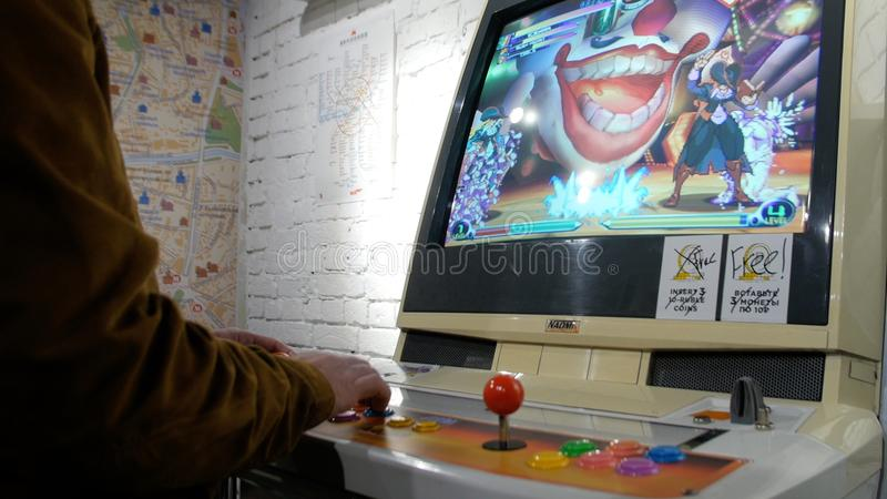 Man playing old game console. Joystick of a vintage arcade videogame - Coin-Op. Close-up of man playing arcade games royalty free stock photo