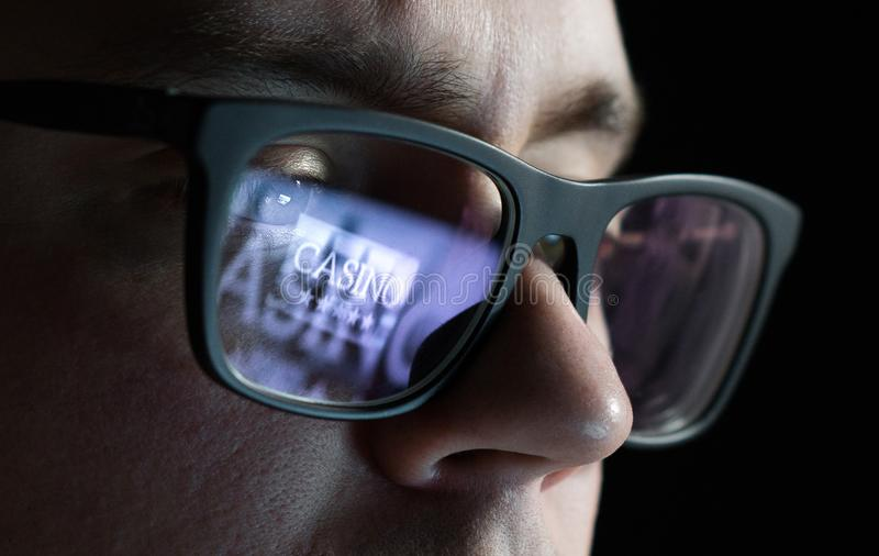 Man playing online casino games late at night. Gambling problem and addiction concept. Addict with reflection of laptop screen on glasses stock image