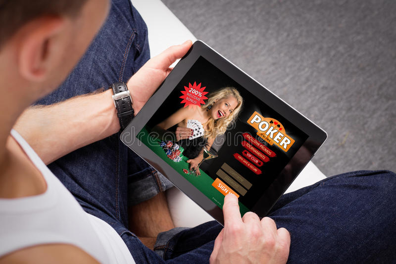Man playing poker on tablet stock photography