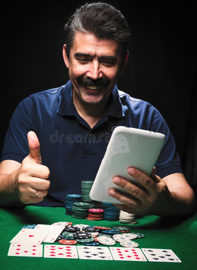 Man is playing poker with tablet online. Emotional card player royalty free stock photo