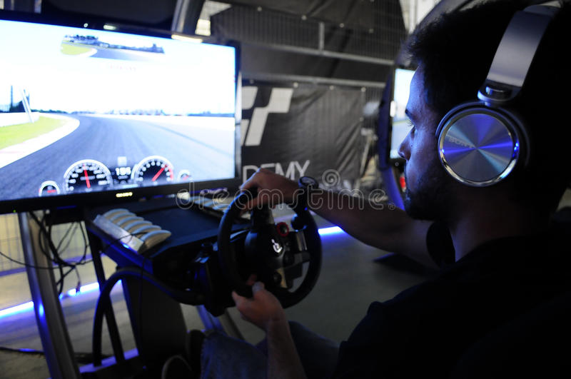 Man Playing a Race Cars Game. Modern driving simulator for PS4. In 2014, PlayStation Portugal and GT Academy launched a challenge to find another pilot who can royalty free stock image