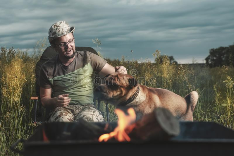 Man playing with a Shar Pei dog outdoors in the light of fire stock photos