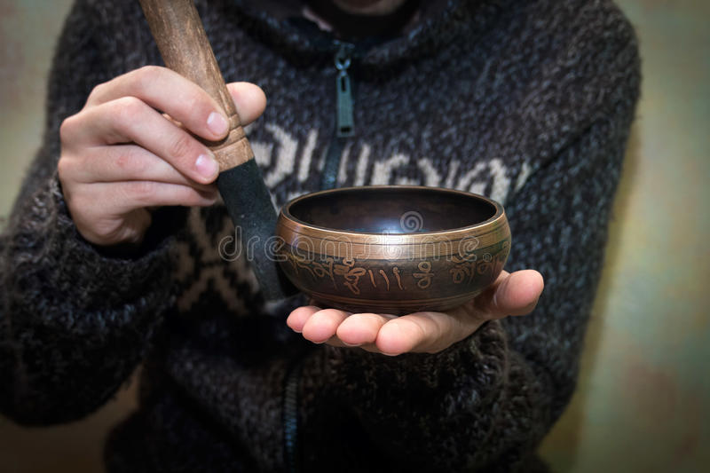 Man playing on a singing bowl. Man sitting in yoga studio and playing on a singing bowl stock images