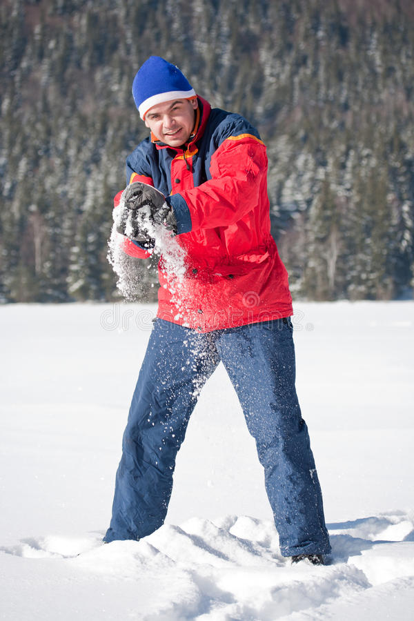 Man playing with snowballs stock photo
