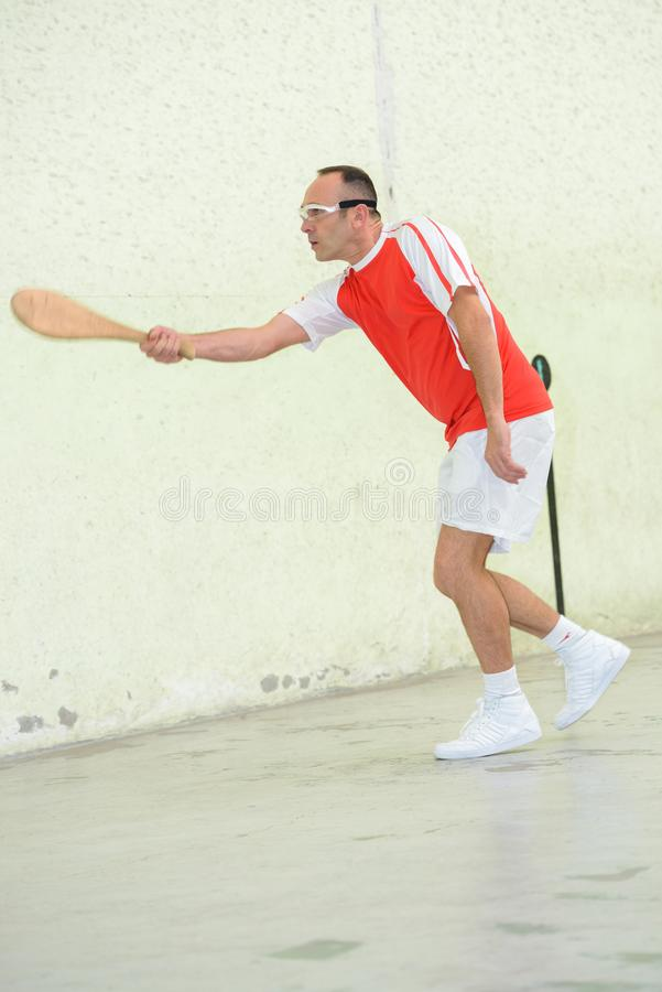 Man playing squash with wood racket royalty free stock photos