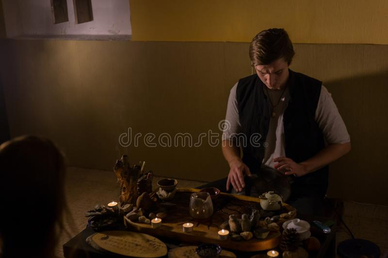 Man playing hang drum. Man playing tank drum or hang at home. Warm romantic illumination, low key. Relaxation, meditative and traditional music concept. Close up stock photo