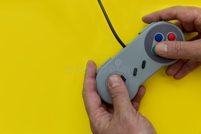 Man playing video game with controller yellow background royalty free stock images