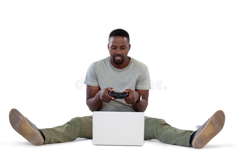 Man playing video game on laptop royalty free stock images