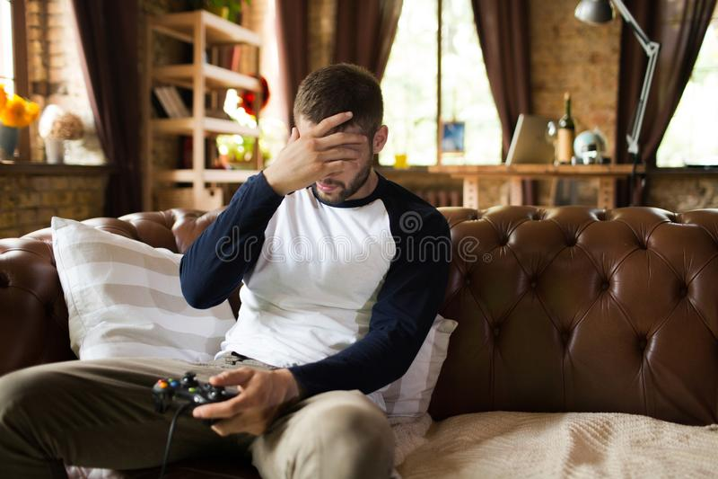 Man playing video games being upset losing game round. royalty free stock image