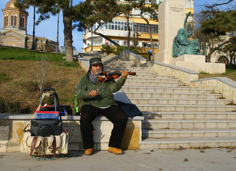 Man playing the violin and enchant visitors. CONSTANTA,ROMANIA - DECEMBER 12, 2014. Beautiful winter day on the waterfront at the Black Sea in Constanta City stock images