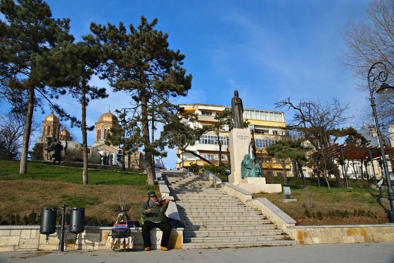 Man playing the violin and enchant visitors. CONSTANTA,ROMANIA - DECEMBER 12, 2014. Beautiful winter day on the waterfront at the Black Sea in Constanta City royalty free stock photos