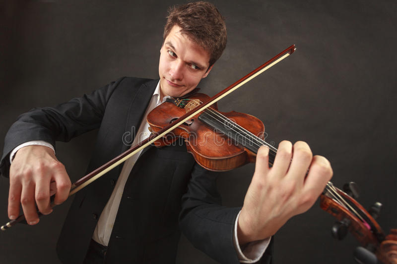 Man playing violin showing emotions and expressions. Music passion, hobby concept. Man playing violin showing funny emotions and face expressions. Studio shot on royalty free stock photos