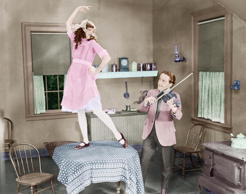 Man playing violin for woman dancing on table royalty free stock photo