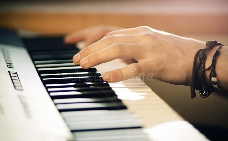 A man plays a beautiful arrangement of the melody on the synthesizer. A man with a brown bracelet on his hand plays a beautiful arrangement of the melody on the royalty free stock image