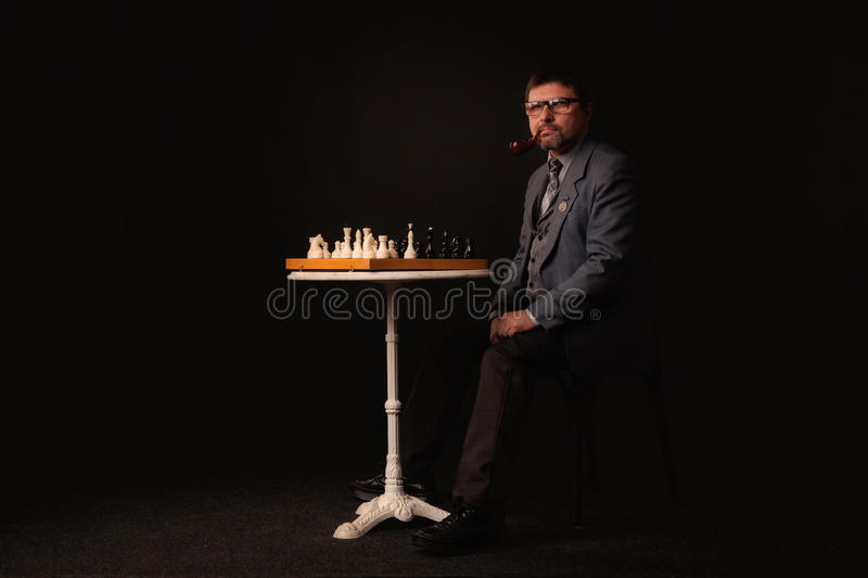A man plays chess and smokes a pipe on a dark background stock photography